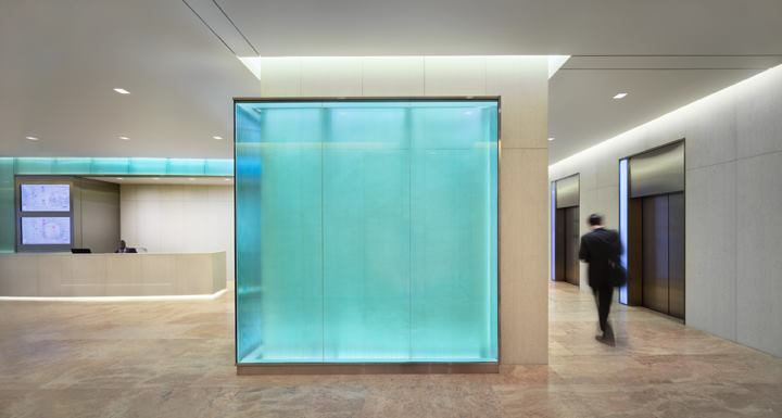 A backlit, glass-walled corner guides building patrons to the elevator bank.