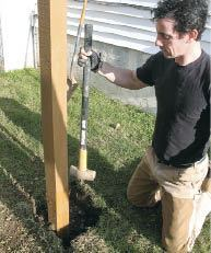 Figure 3. The bottoms of the posts rest on gravel for drainage and are topped with a bag of quick-setting concrete to keep them steady. Tamping the soil adds more stability and minimizes setting.