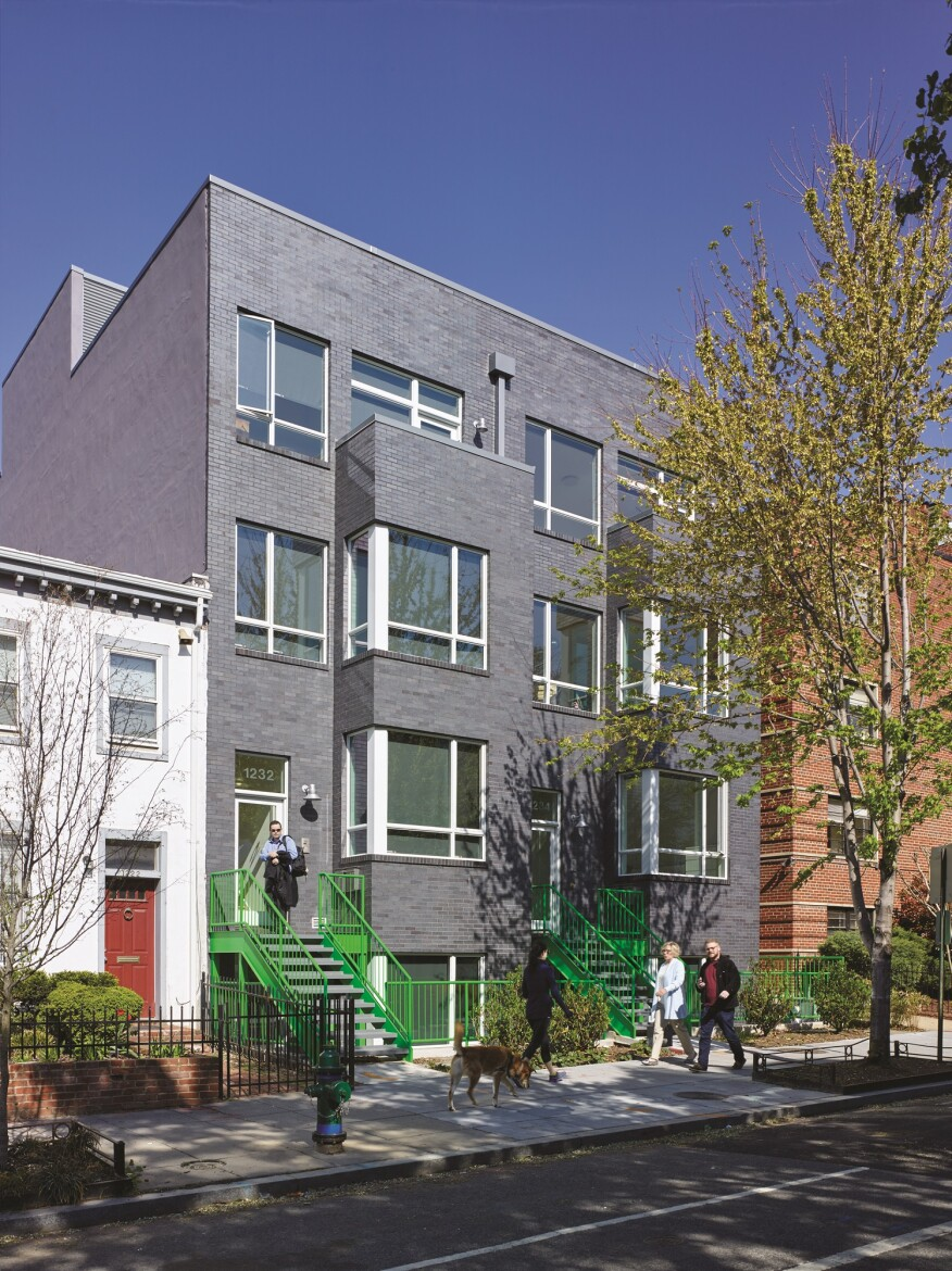 The infill duplexes at 1232–1234 10th St. are finished in manganese iron spot brick in the front (shown) and weathered zinc in the back.