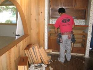 A crew member carefully disassembles old cabinetry during one of Daniel Mackey's renovation projects.