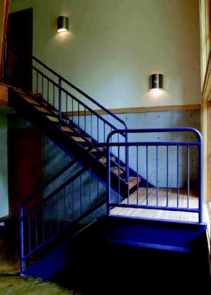 ART BUILT IN: Little splurges include a staircase fabricated by a local steel artist and  a stained, patterned concrete floor inlaid with bronze screeds. Forming ties  in the concrete wall behind the stairs were left exposed in the masonry to  create a dot pattern.