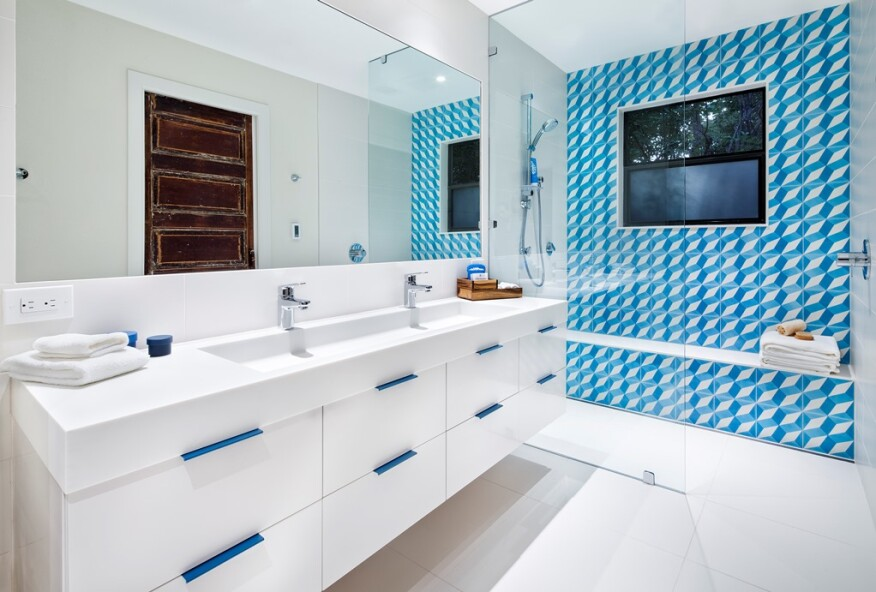 Bright blue tiles and coordinating drawer pulls provide a pop of color in this bathroom remodel by Mark Evans