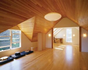 Beaded fir paneling takes center stage in the second-floor studio, where it highlights the angular geometry of the dormered roof.