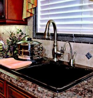 STATION AGENTS: A kitchen this large needs multiple prep areas: InSync has three stations outfitted  with products from the Kohler Co.: a Pro Cookcenter self-rimming sink  that also performs water-based cooking (shown); a cast-iron Smart Divide  sink with a low-profile basin divider; and a 33-inch undercounter stainless  steel trough sink. All three stations have Kohler's Vinnata faucet with  its high arc and a pull-down spray head.