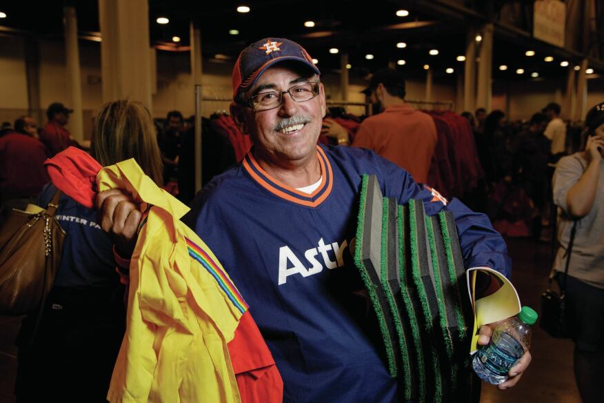 Armando Santana holds up turf and jackets he purchased at the firesale.