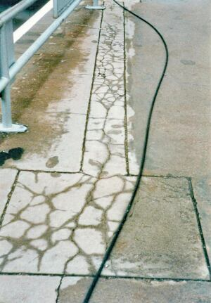 As water leaves the repair material, through evaporation or absorption into the existing concrete, the repair material loses volume. This drying shrinkage may cause the repair to crack, as it did in this project.