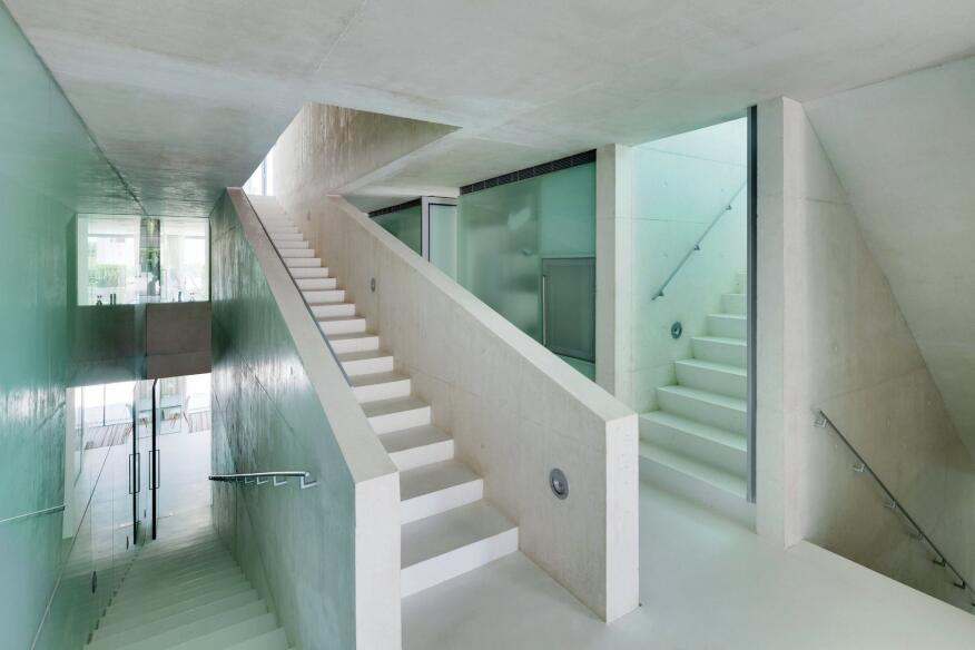 "Circulation through the house follows two paths, a ""fast stair"" that moves directly from the basement level to the pool (seen at right), and a ""slow stair,"" with deeper risers, that winds through the interior (at left)."
