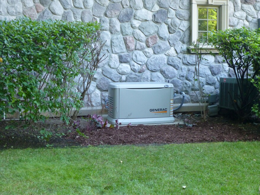 A standby home generator from the Generac Guardian series installed at a lakeside home.