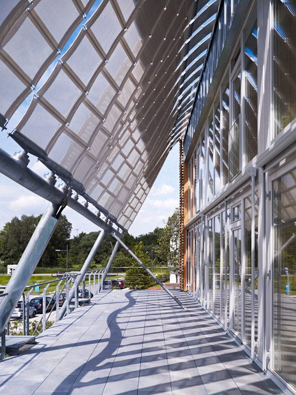 Flexible photovoltaics are mounted on textile ribbons that form a canopy over terraces on the second floor.