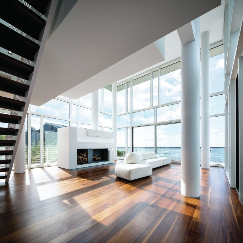 The double-height living room faces the water, and a large built-in fireplace helps ward off winter chill for a year-round experience.