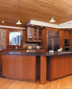 The pillars in the open kitchen echo the posts on the adjacent deck. The living room and kitchen's combination of wood tones creates a warm atmosphere.