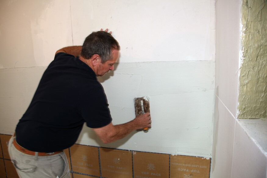 Thinset is applied to the wall in accordance with the tile manufacturer's instructions.