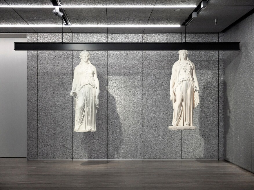 Suspended caryatids viewed against a foamed aluminum backdrop.