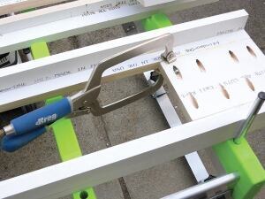 The gridlike top makes it possible to clamp in from the edge of the table without blocking the material off the surface. The vertical piece on the right is a riser peg; it's being used as a stop.
