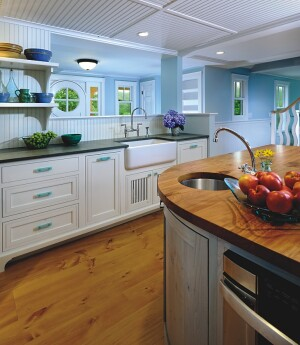 The placement of the prep sink on the curve of the island allows for more usuable space in the kitchen, while materials such as the reclaimed beech countertop add to the green qualities of the kitchen.