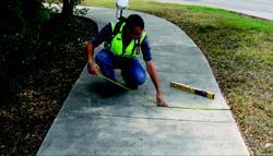 A field technician checks the width of a sidewalk for compliance with ADA guidelines. Photo: Shawn  Devereaux