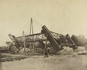 Gustave Eiffel stands by a pier of the Eiffel tower during its construction (circa 1887)