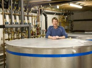 Homeowner Chris Anderson with large solar thermal water storage tanks in the basement of his Peterborough, N.H., home.