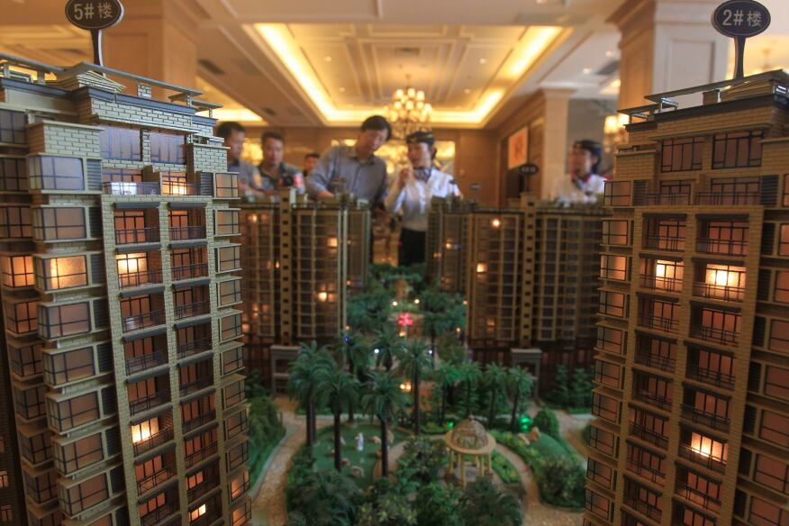 Chinese homebuyers look at models of apartment buildings during a real estate fair in Haikou City in China's Hainan province on Nov. 29. According to a recent survey, China's housing prices fell on a monthly basis for the seventh straight month in November, with the market yet to feel the full impact of an interest rate cut. The average price of a new home in China's 100 major cities was 10,589 yuan ($1,736) per square metre in November, down 0.38 percent from October, according to the China Index Academy.