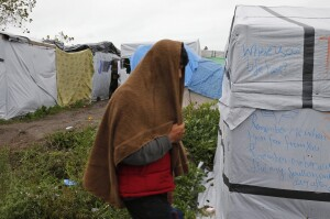 "A migrant walks past tents and shelters in the makeshift camp called the ""New Jungle"" as unseasonably cool temperatures arrive in Calais, northern France, October 21, 2015. The number of migrants camped on France's north coast near Calais has doubled to around 6,000 in recent weeks, boosted by an influx across Europe's borders. Migrants and refugees are camped in Calais, fleeing war and poverty in the Middle East, Africa and Asia and now living in the jungle. Most of them are hoping to make the crossing to England.   REUTERS/Pascal Rossignol - RTS5GCR"