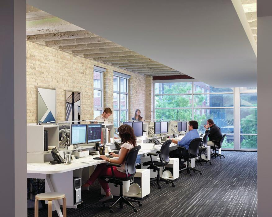 The second floor is the firm's main studio space. A dropped soffit was added to the exposed concrete ceiling to hide wiring and ductwork; and dividing walls were removed to open up the space. The Chicago-common-brick walls are decorated with photographs of one of the firm's residential projects. The office furniture is from Watson (a budget alternative to Herman Miller Canvas) and the flooring is Milliken carpet tiles.