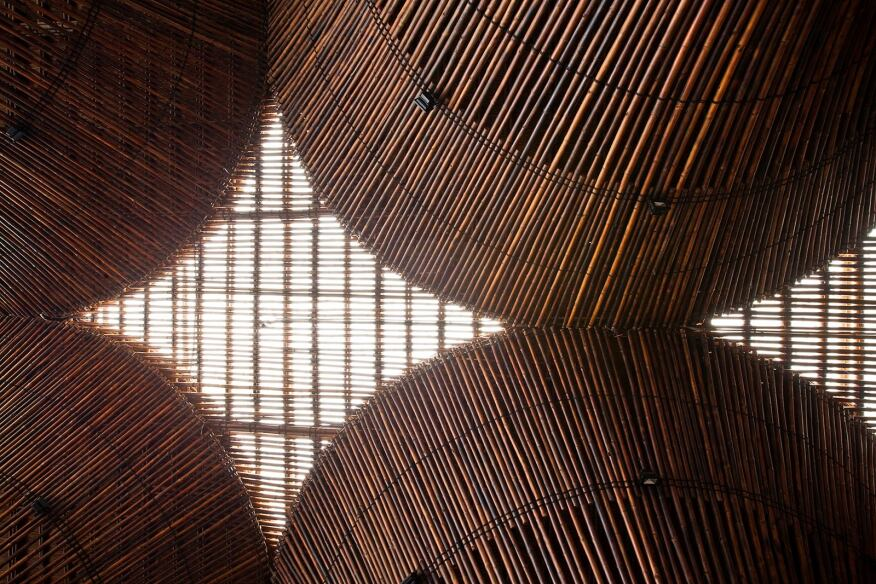 The bamboo columns support a roof made of fiber-reinforced plastic panels and thatch.