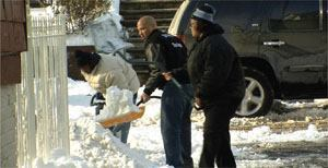On New Year's Eve, 2009, Newark, N.J., Mayor Cory Booker (center) responded to a constituent's Twitter message calling on him to help her father shovel his driveway; volunteers that had seen the exchange of tweets joined in to help. Photo: City of Newark