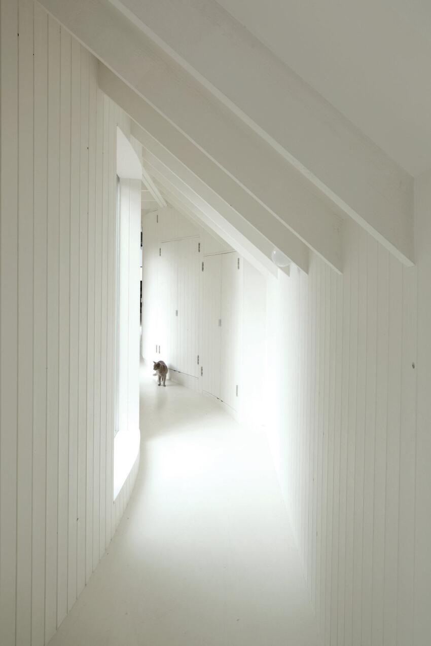The interior of the timber-frame addition is also clad floor-to-ceiling in wood. The panels are painted white to maximize the daylight that enters through the south-facing windows. This hallway leads from a new bedroom suite back to the glazed ramp and historic cottages.