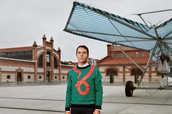 """Andrés Jaque poses in front of his firm's """"Escaravox"""" project. Jaque purchased a series of winged rolling irrigation platforms, added speakers, wiring and lighting, and staged them in a public square in Madrid. Musicians, DJs, writers, and actors used them to plug in equipment and hold impromptu readings and performances."""