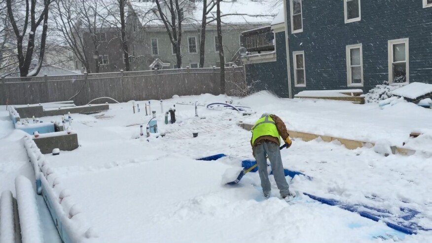 A worker shovels snow from the insulated subgrade at a Great Falls infill project in Portland, Maine, after a sudden March snowfall.