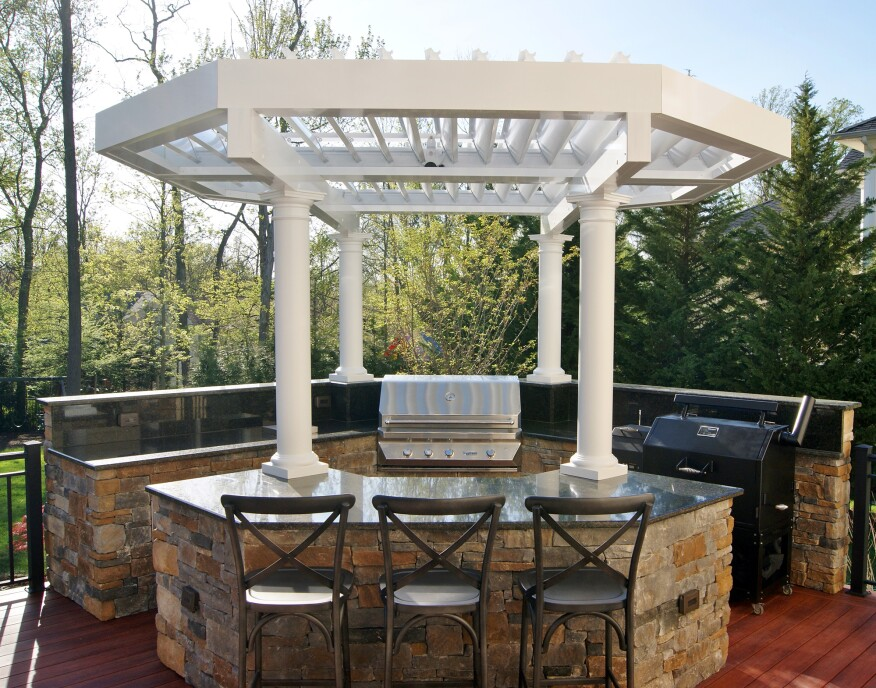 This outdoor kitchen features granite countertops and cabinets faced with stacked stone. Rain or shine, shelter is provided by an Equinox louvered octagonal pergola, supported by custom PVC columns.