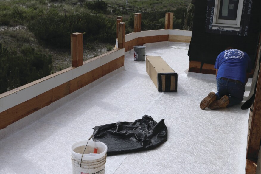 After the resin was allowed to cure for a day and then sanded smooth and thoroughly vacuumed, a layer of 1.5-ounce chopped fiberglass mat was spread out over the deck surface. Note how the mat extends up the parapet walls, to create a pan.