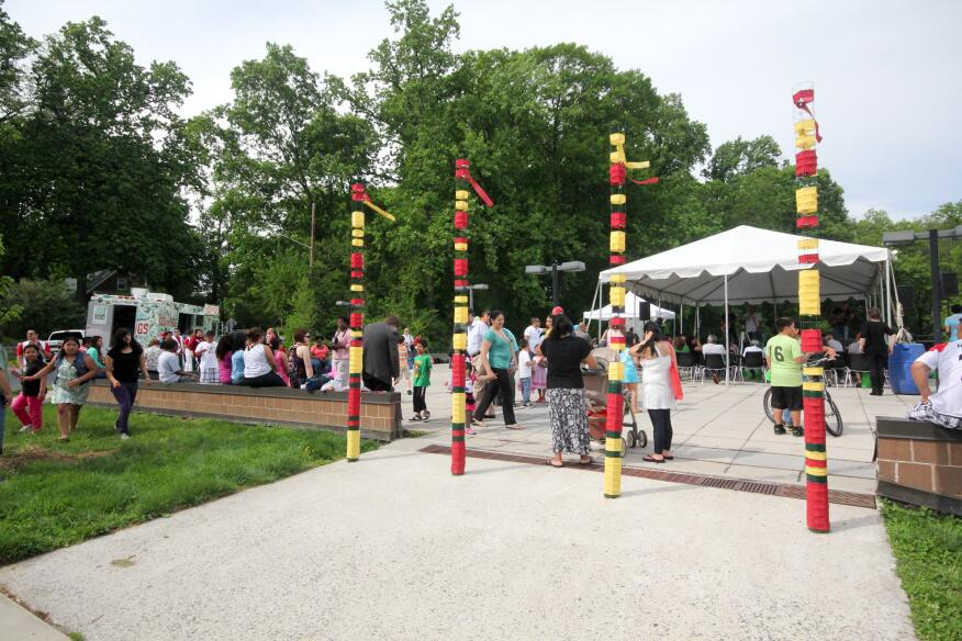 Totems  Situated at the entrance to the library plaza, these story-tall pillars are wrapped in alternating stripes of red, green, and yellow material. Drawing the eye to the entrance to the long-disused public space outside the Long Branch Library, the installation aims to activate the area, inviting people to come and explore the renovated space.