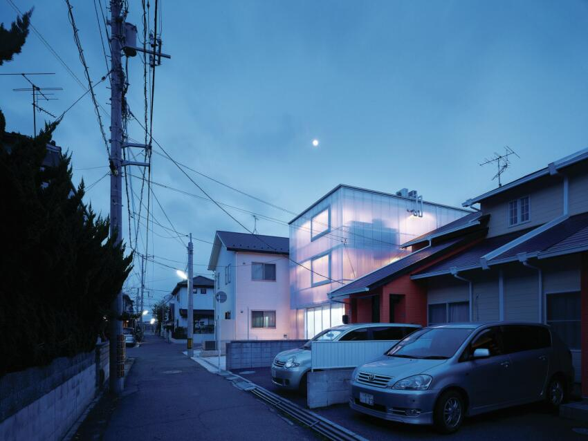 Seen here at dusk, the interior lights in the House in Tousuien make the polycarbonate-clad structure glow amid the quiet Hiroshima neighborhood.