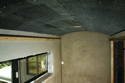 To waterproof the ceiling, a layer of cold-patch tar is spread over the green board followed by a layer of 30-pound felt paper. Wire mesh is then nailed in over the entire surface.