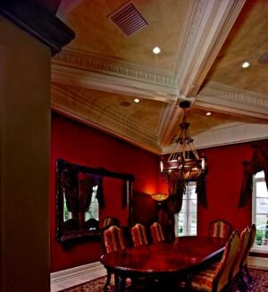 "TO DINE FOR: The ceiling treatment in the regal dining room with a formal table is as commanding  as the view to the outdoors. Ornamental tiers of Fypon decorative  crown molding look like natural, carved wood. ""We used satin finish faux  painting, making no attempt to cover up the seams, as natural wood would  show the seams,"" says interior designer Donnie Saxon."