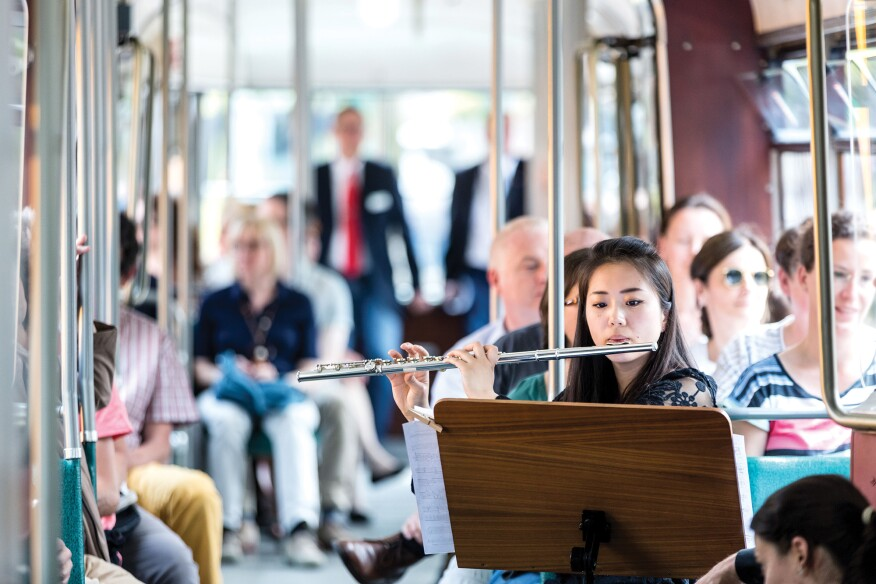A flutist performing on a city tram