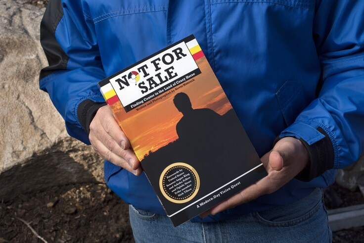 "Kevin Hancock holds his book, ""Not For Sale: Finding Center in the Land of Crazy Horse"" about his experiences on the Pine Ridge Indian Reservation and with the Oglala Sioux tribe."