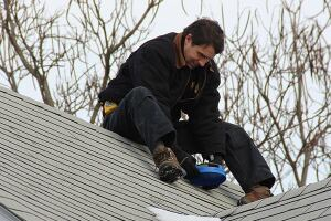 ReVision Energy's Phil Coupe checks the solar exposure of a rooftop on Peaks Island, in Portland, Maine. Solar arrays combined with mini-split air-source heat pumps have helped some island residents drastically cut back their consumption of costly heating oil.