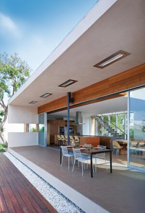 Occupying the full width of its wing, the kitchen/dining/sitting space opens onto a full-length poolside veranda.
