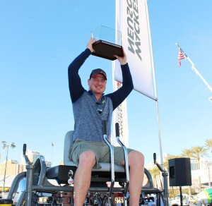 Wacker Neuson's 2015 Trowel Challenge grand prize winner, Greg Geiger, owner of On Demand Concrete Solutions, Warburg, Alberta, Canada, celebrates on the company's new 48-inch CRT 38-35VX ride-on trowel and hoists his first place finish trophy after winning the annual competition at the World of Concrete in Las Vegas.