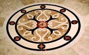 MARBLE MAGIC: The house has a large number of architectural details, including a travertine  floor medallion, stair inserts, and custom marble fireplace surrounds by  Cuellar USA, a Cosentino company. The floor medallion and stair inserts (below) are  made of Rojo Alhama and Nazari travertine, Crema Marfil marble, and black  granite, the loggia/ summer kitchen has a Gris Viola marble fireplace and  TV surround, and the living room fireplace (bottom) is made from a single block of Rojo  Alhama travertine. www.cuellarusa.com
