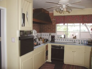 "Stylistically, the Donalds didnít draw much inspiration from their 1955 kitchen (above), but it did serve as fodder for any number of practical things down the line in the remodel. The beadboard on the ceiling found a second life as window trim, the old mahogany cabinet shelves were planed to create ""new"" baseboards, and building materials down to the studs were saved to frame in the kitchen. Sustainable features in the new kitchen include a Marmoleum floor and a beech island countertop that was once part of an elementary school floor."