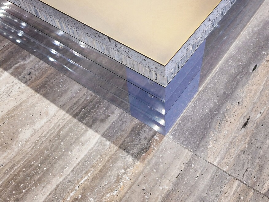 Detail of a gallery platform: plate metal on travertine, unfinished honeycomb aluminum, and solid polished acrylic.