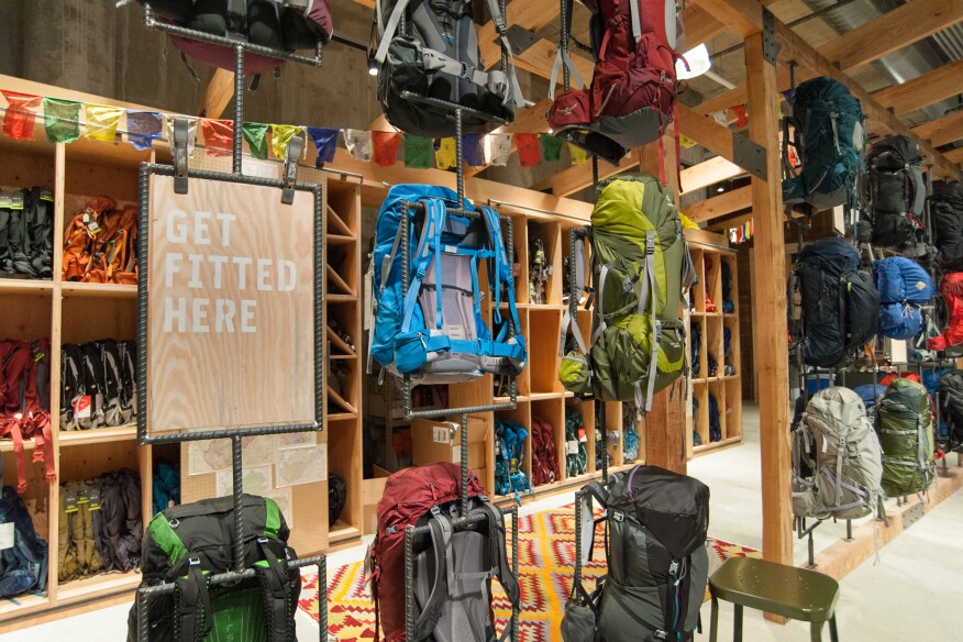 Custom rotatable display racks made of rebar allow visitors to see all sides of backpacks.