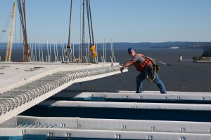 A worker helps guide the placement of a prefabricated concrete road deck panel that is bonded to structural steel underneath and connects via rebar extending from each panel.