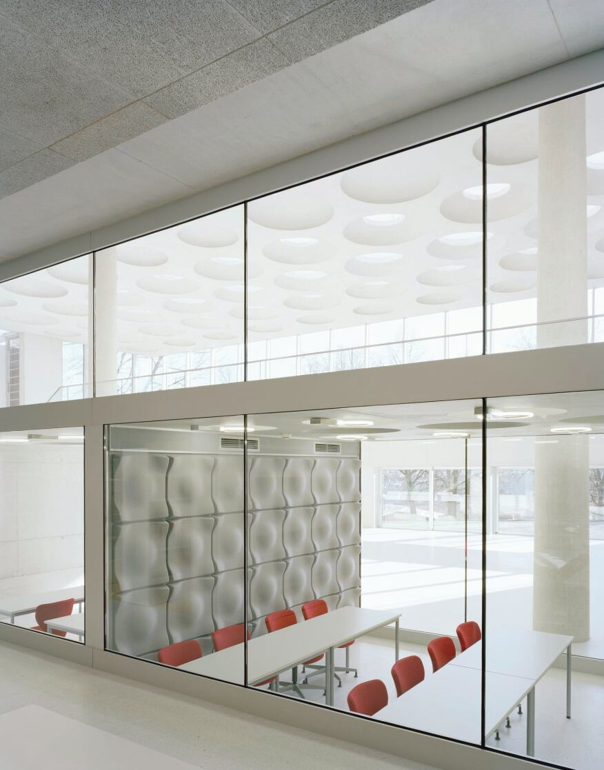 View through the library's glass walls and into the first floor multipurpose rooms, and on the light-inscribed walkway above.