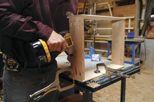 Pocket hole joiney begins with drilling steep-angled holes with a special jig and drill bit. Pieces are joined temporarily with quick-release clamps while the screws are driven.