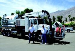 Vince Martinez (left) and Barry Adams, both with Orange County, work with a Vactor sewer cleaner that runs on compressed natural gas that meets air quality requirements.