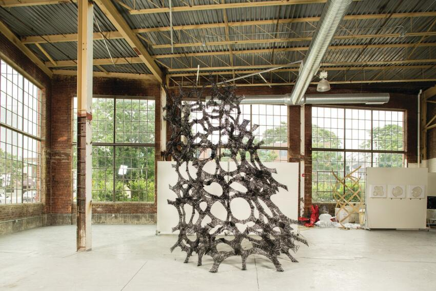 Area sculpted the 14-foot-tall, 8-foot-wide, and 31-pound C-Lith installation from carbon fiber pre-impregnated with epoxy resin. The structure's form was derived from a packed tetrahedral base geometry.
